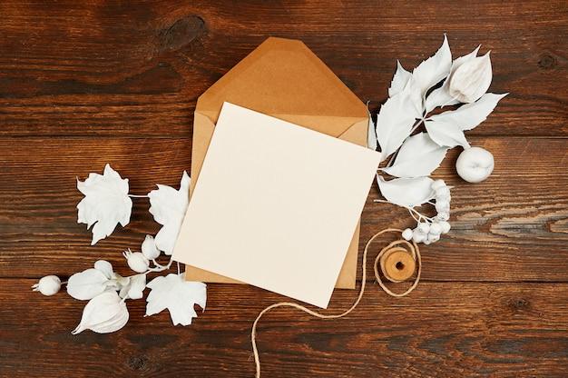 Brief blankopapier in grünen umschlag mit hölzernen schneeflocken und geschenkboxen auf holztisch