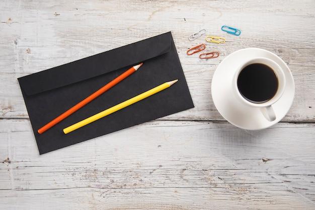 Brief mit stiften und tasse kaffee auf dem tisch