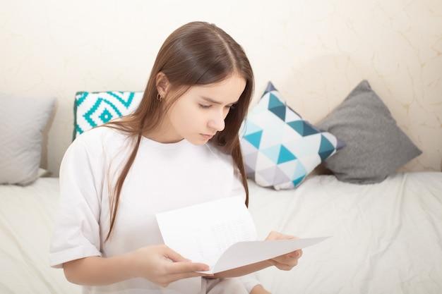 Brief, notiz. mädchen liest zu hause ein blatt papier, schaut sorgfältig in den text