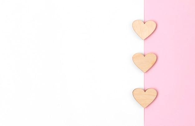 Brief oder grußkarte mit holzherzen auf pastellrosa tisch