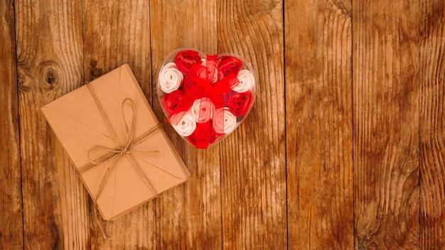 Briefe in bastelpapierumschlägen und ein geschenk von rosen auf holz
