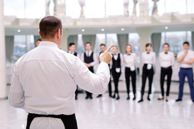 Briefing im restaurant. der küchenchef informiert das restaurant. er interagiert mit dem küchenchef in der gewerblichen küche