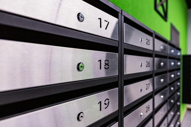 Briefkästen in einem wohnhaus aus edelstahl an einer grünen wand
