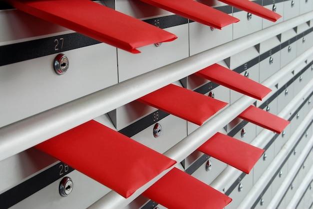 Briefkästen in reihen mit buchstaben in roten umschlägen