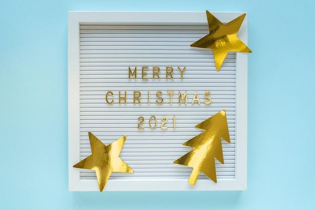 Briefkarton mit frohe weihnachten 2021 gruß, dekorationen auf blau pastellfarbenem mädchenhintergrund. weihnachtskomposition. flach von oben liegen