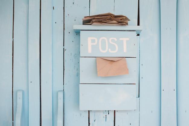 Briefkasten mit buchstaben in der weinleseart auf hölzernem blau