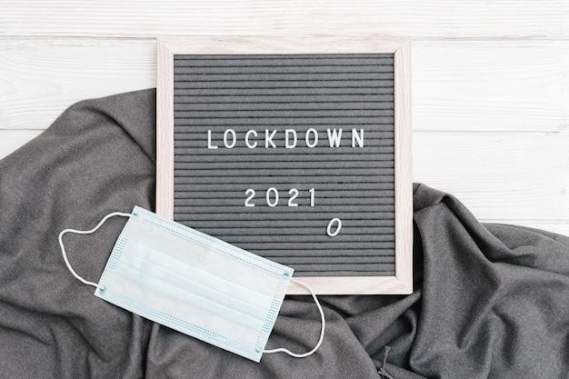 Briefkasten mit nachrichtentext-sperre 2021 und schützender gesichtsmaske. social media inhalte.