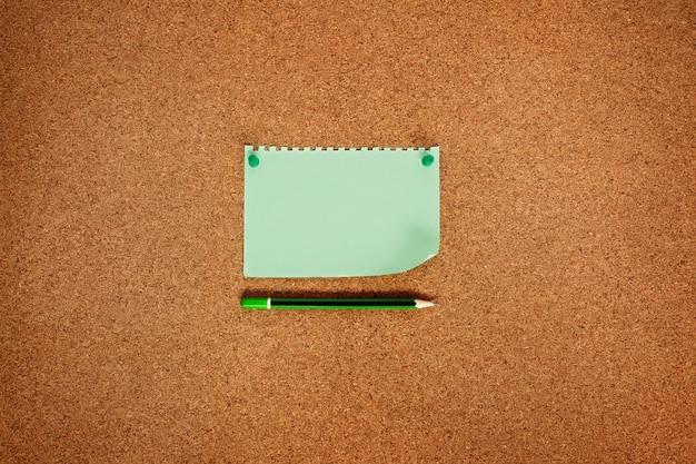 Briefpapier mit grünen knöpfen und einem korkenbrettbleistift, draufsicht