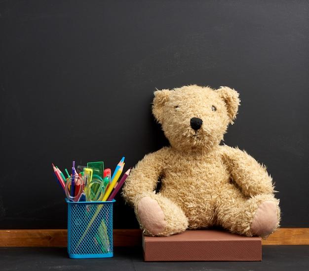 Briefpapier und brauner teddybär sitzen auf dem raum einer leeren schwarzen kreidetafel