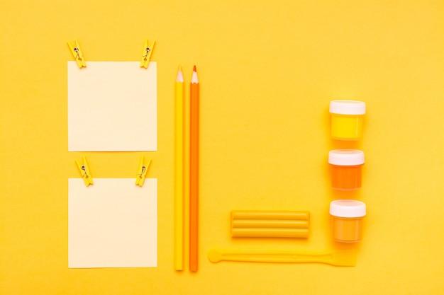 Briefpapierblätter für die anmerkungen befestigt, bleistift, filzstift, gouache, plasticine und stapel auf einer gelben draufsicht
