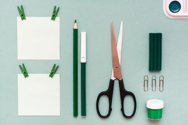 Briefpapierblätter für die anmerkungen befestigt, bleistift, filzstift, scheren, gouache, plasticine und aquarell auf einer grünen draufsicht
