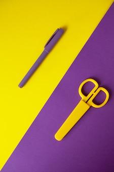 Briefpapierscheren des gelben kindes auf purpurrotem hintergrund, purpurroter stift auf gelbem hintergrund.