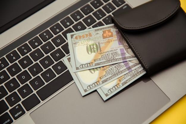 Brieftasche mit geld auf der tastatur. online einkaufen.