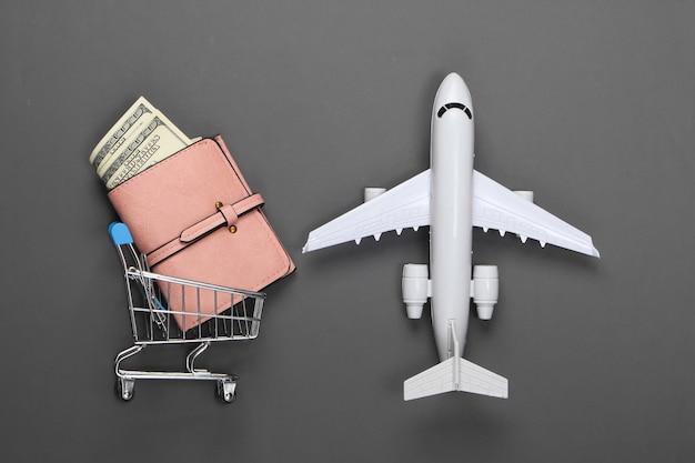 Brieftasche mit geld in einem einkaufswagen und figur eines passagierflugzeugs auf einem grau. logistik- oder reisekonzept