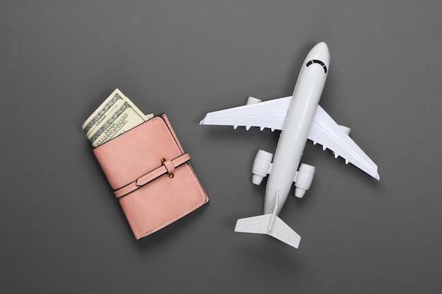 Brieftasche mit geld und figur eines passagierflugzeugs auf einem grau.