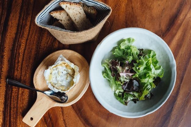 Briekäse auf hölzernem brett diente mit grünem eichensalat und frischem gebackenem geschnittenem brot.