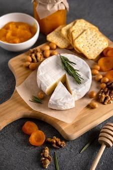 Briekäse mit nüssen, birnenscheiben und getrockneten aprikosen. camembertkäse. brie-käse oder camembert-käse auf einem holzbrett. leckere käsestarter.