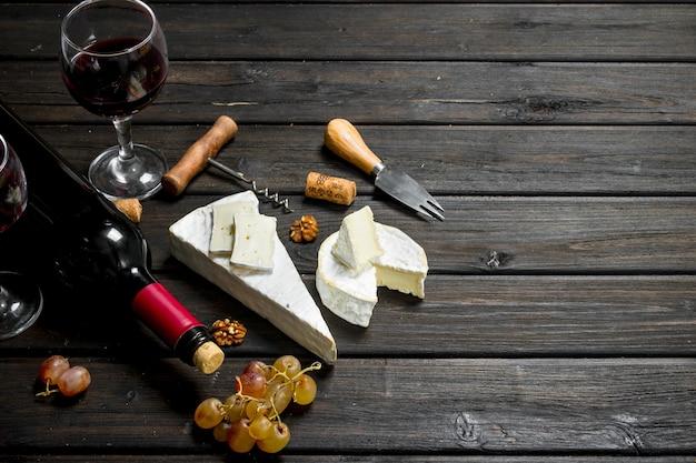 Briekäse mit rotwein, nüssen und trauben auf holztisch.