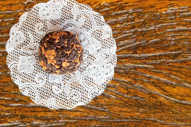 Brigadeiro. süße kondensmilch mit schokolade und kaffee, auf detail von putz und hölzernem hintergrund.