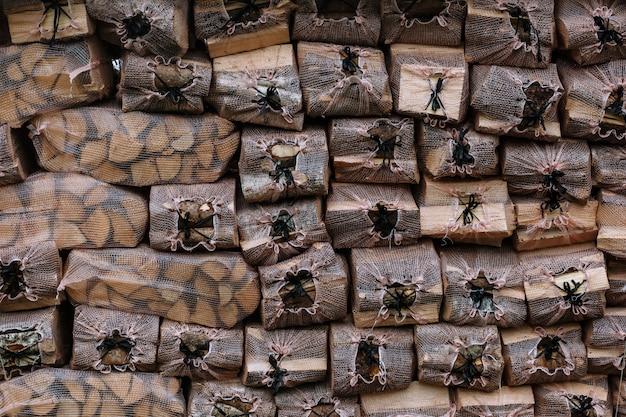 Briketts mit brennholz. brennholz in transparenten netzbeuteln