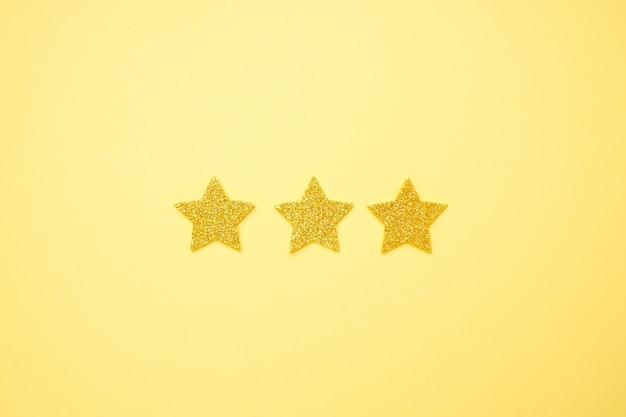 Brillante glitzersterne auf hellem gelb, bewertung 3 sterne