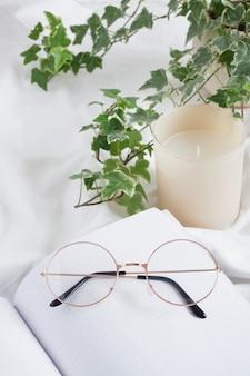 Brille, aromakerze, blume in einem topf und offener leerer notizblock auf weißem zerknittertem tuch, bequem zu hause planen und arbeiten