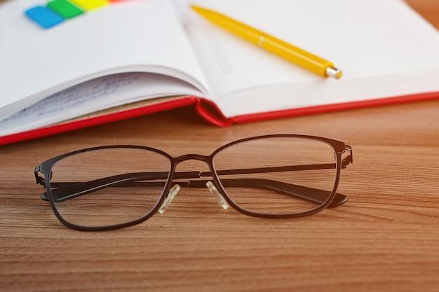 Brille auf dem desktop mit einem notizbuch im hintergrund