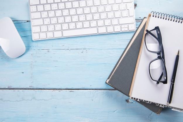 Brille auf notizblock auf buch mit computer auf tisch