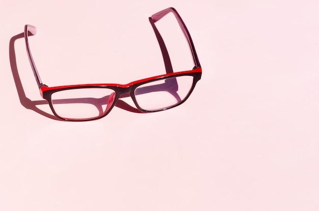 Brille auf rosa hintergrund mit schatten unter dem natürlichen licht