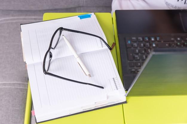 Brille, die auf dem laptoptisch in der nähe einer offenen leeren seite eines tagebuchs mit einem stift liegt, um termine zu vereinbaren, einen zeitplan zu organisieren