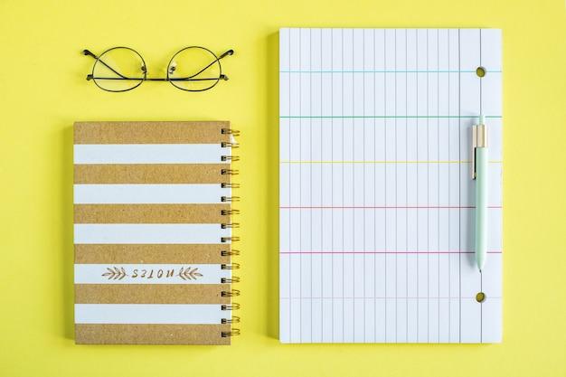 Brille, geschlossenes notizbuch mit spiralbinder, stift und liniertem papier auf gelbem hintergrund