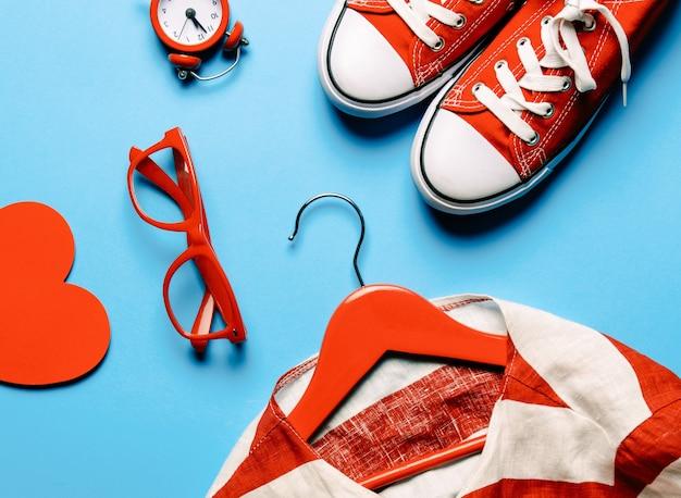 Brille, herzförmiges spielzeug, uhr, gummischuhe, jacke auf dem kleiderbügel und laptop auf dem blau