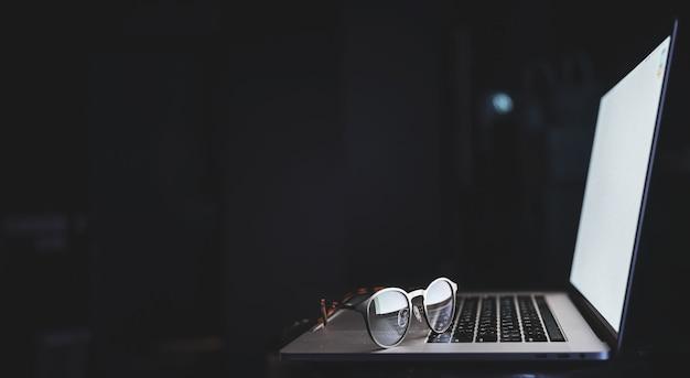 Brille liegt auf dem laptop und reflektiert licht vom bildschirm im dunkeln, kopierraum.