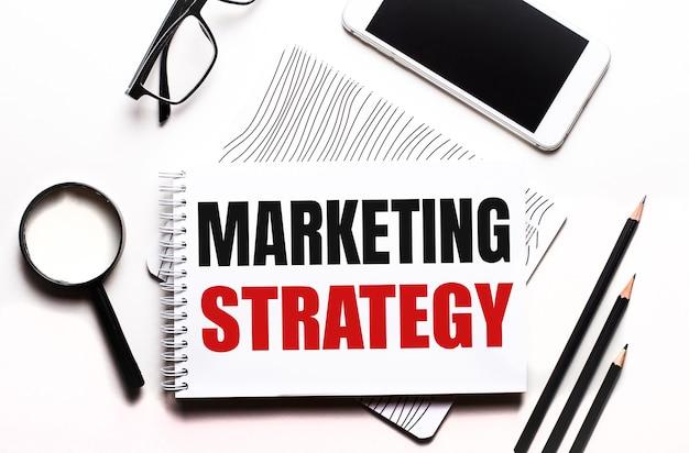 Brille, lupe, bleistifte, smartphone und notizbuch mit text marketing strategy