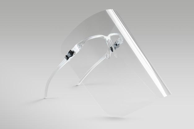 Brille mit abnehmbarem gesichtsschutz auf grauem hintergrund