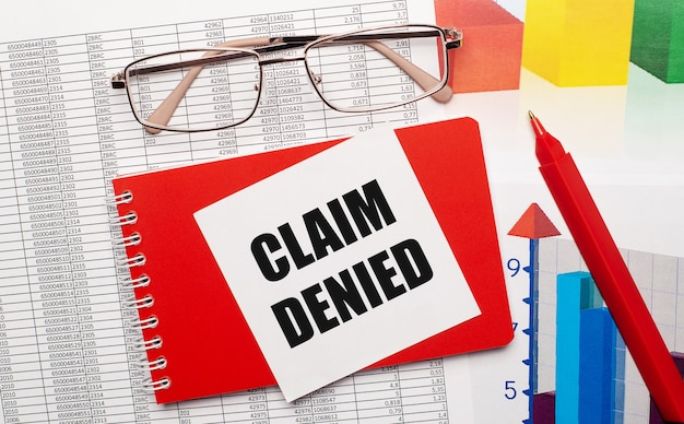 Brille mit goldrand, ein roter stift, farbtabellen und ein rotes notizbuch mit einer weißen karte mit dem text claim denied