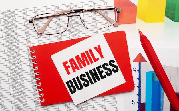 Brille mit goldrand, ein roter stift, farbtabellen und ein rotes notizbuch mit einer weißen karte mit dem text family business auf dem desktop