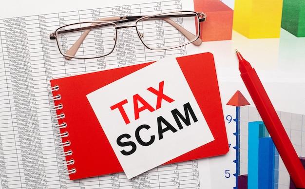 Brille mit goldrand, ein roter stift, farbtabellen und ein rotes notizbuch mit einer weißen karte mit dem text tax scam auf dem desktop. geschäftskonzept. von oben betrachten