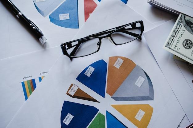 Brille, stift mit vielen diagrammen und grafiken. reflektionslicht und aufflackern. konzeptbild des sammelns der daten und des statistischen arbeitens.