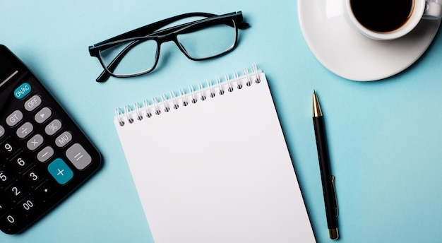Brille, taschenrechner, leeres notizbuch und stift auf hellblau. speicherplatz kopieren