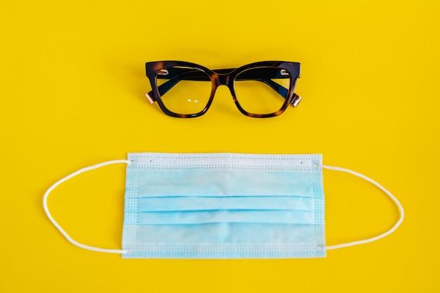 Brille und maske imitieren gesicht auf gelbem hintergrund