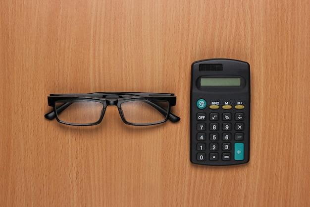 Brille und taschenrechner auf dem schreibtisch. draufsicht