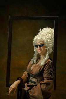 Brillen anprobieren. porträt der mittelalterlichen jungen frau in der weinlesekleidung mit holzrahmen auf dunklem hintergrund. weibliches modell als herzogin, königliche person. konzept des vergleichs von epochen, mode, schönheit.