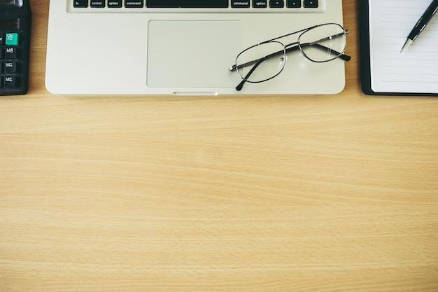 Brillen auf laptop-tastatur mit taschenrechner und stift-tagebuch auf holztisch