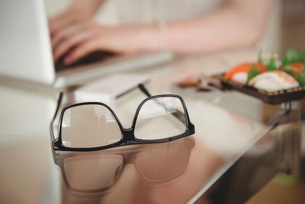 Brillen auf tisch gegen frau mit laptop