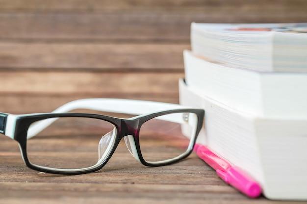 Brillen auf unscharfen büchern und holzbretthintergrund