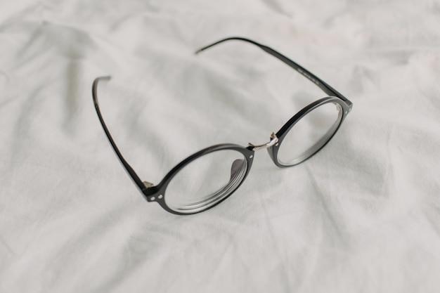 Brillen mit schwarzem plastiktempel auf weißem bettlaken.