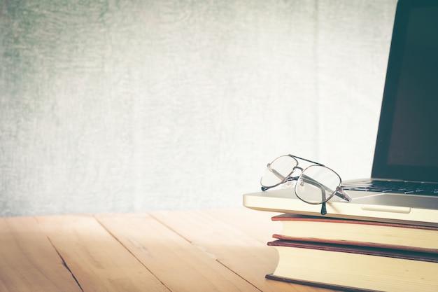 Brillen und bücher auf tafelhintergrund