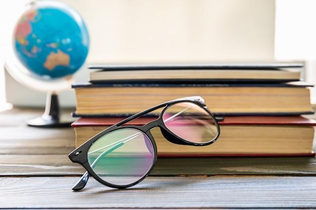 Brillen und bücher neben dem fenster