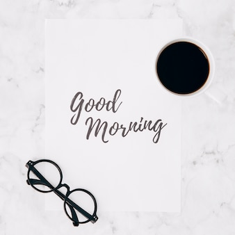 Brillen und kaffeetasse über dem guten morgen simsen auf papier über weißem marmorstrukturhintergrund